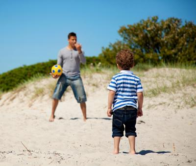 Child Looking at His Dad Teaching Him Soccer