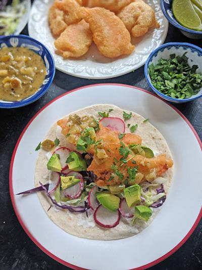 Beer-battered shrimp are stuffed into a flour tortilla with shredded cabbage, lime crema, avocado, and salsa verde for a Lenten taco.