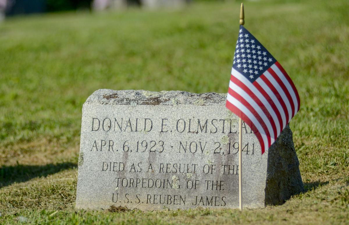 A flag waves above the grave of Donald Olmstead
