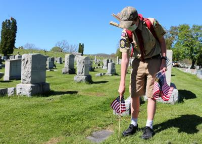 Boy Scouts place American flags at veterans graves at St. Bonaventure Cemetery
