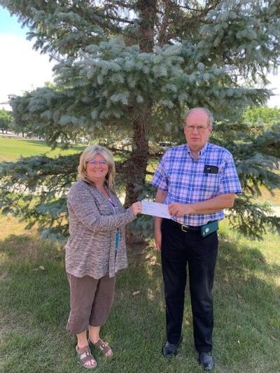 Sully Buttes SPED Instructor Cherie Hill accepts the contribution from the Ruth Bayne Trust from Trustee Mike Owens.