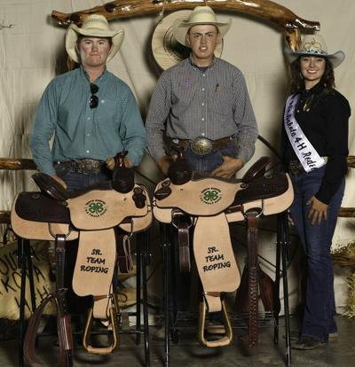 Payden Belkham, left, wins a sadlle for placing 1st in the Sr. Team Roping at the SD 4H Rodeo.