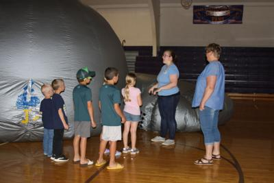 South Dakota Discover Center's Rile Rowse leads summer readers into the mobile planetarium where she told them the story of the constellations Hercules and Draco. The planetarium was the last event in the 'far out' space themed 'Universe of Stories' summer reading program. Librarian Jackie Aspelin read aloud each of the program days, and students worked on a mural of planets and stars.
