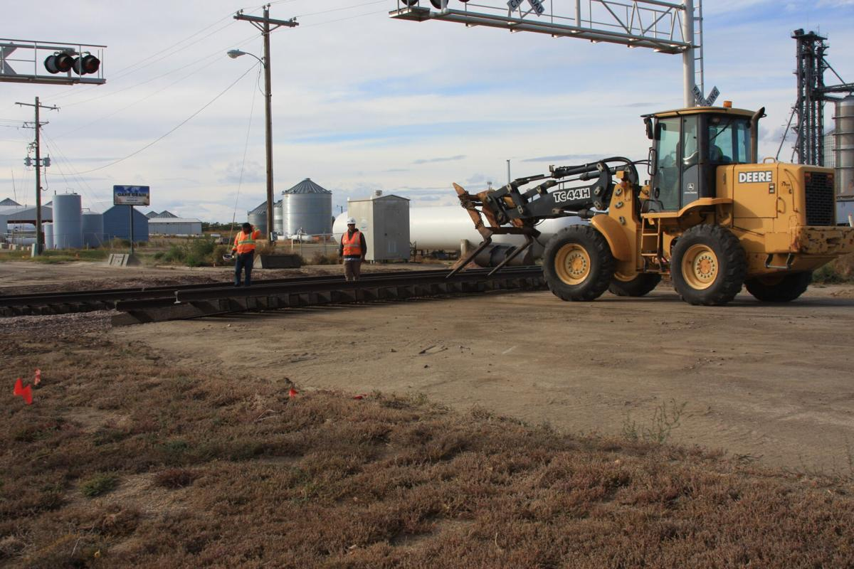 Using a payloader equipped with a fork, the repair crew pushed a new section of track into place.