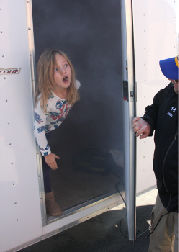Arianna Hill pokes her head outside the smoke-filled trailer for a breath of fresh air.