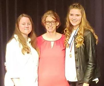 Sully Buttes Oral Interp team members Taryn Kenzy and Lydia Hill flank Coach Melissa Marshall.