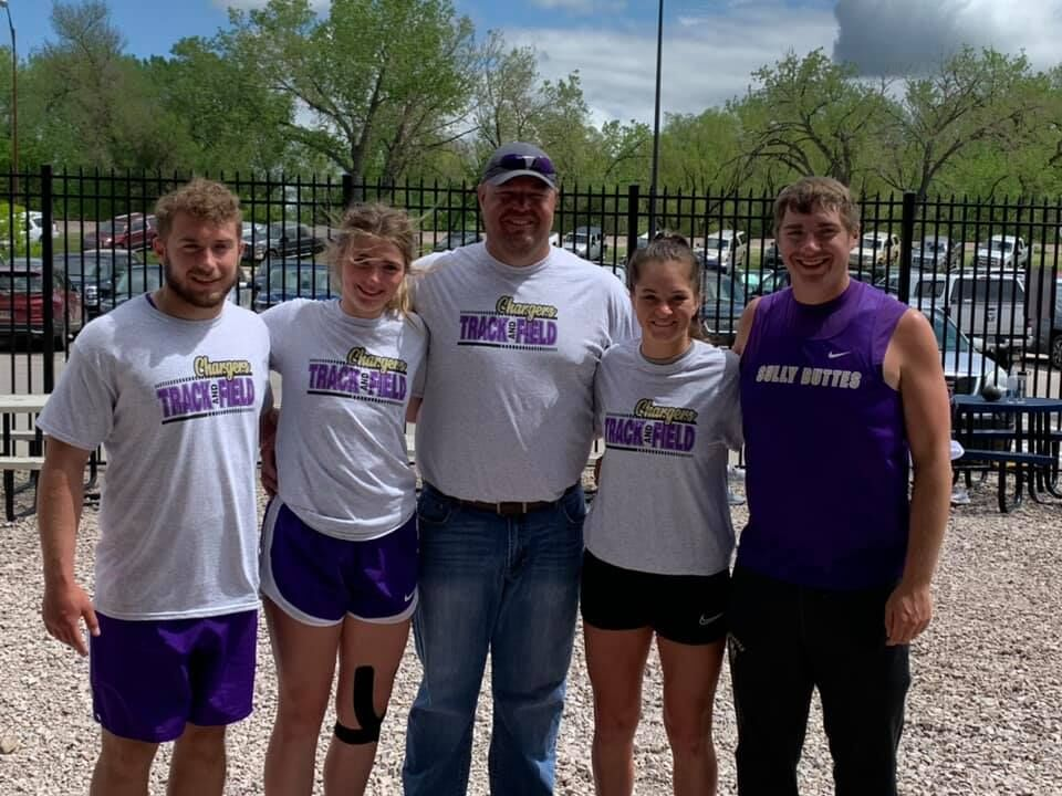 Jordan Schall, Lydia Hill, Coach Moore, Allyson Wittler, and Jesse Schall pose together at State Track as the team of throwers.