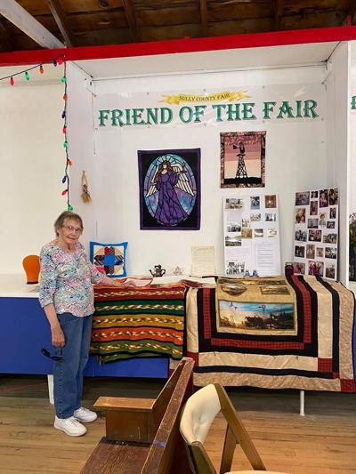 Lila Ludwig stands next to booth that displayed pictures and exhibits from her 75 years involvement in the Sully County Fair.