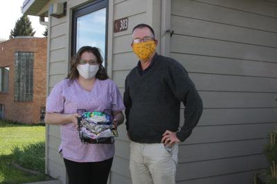RN Jessica Olivier and Dr. Steve Knoble sport masks sewn for the mask drive. The basket Jessica is holding is full of masks which will be distributed to Onida Clinic visitors and patients.