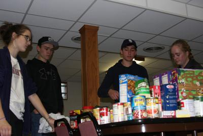 Trichelle White, Griffin Petersen, Garrett Peterson and Caitlin Birney sort the food items that were contributed.