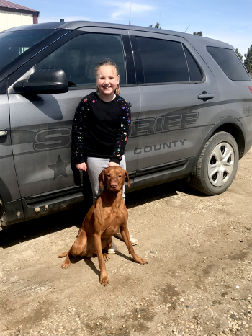 Karmen Merrill poses with Maverick by Deputy Sheriff Curt Olson's cop car.