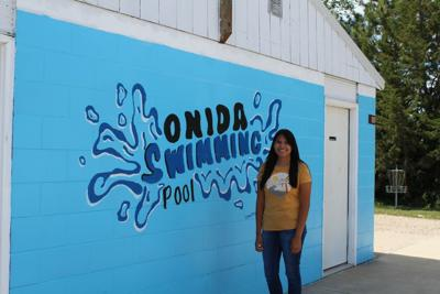 Lexie Marshall pictured next to the mural she created for Onida's swimming pool.