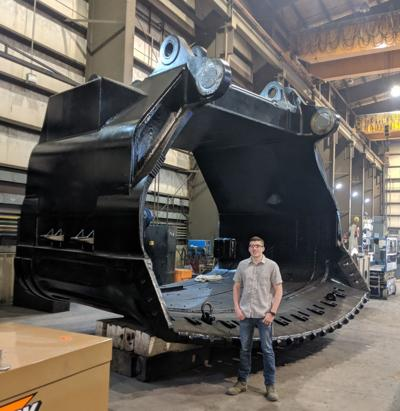 Kole Pickner is pictured in front of a bucket for a coal mining shovel on his first day at L&H Industrial. During his time at L&H, Kole worked with modeling the shovel vehicles it is used on. Kole is pursuing a Mechanical Engineering degree at SDSMT.