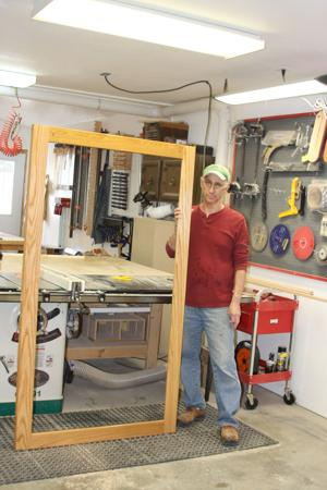 Ken Lyons holds up his latest project, a frame for a church banner.