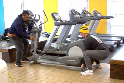 Alex Trujillo and Jesse Birlson moving exercise equipment around at the YMCA.