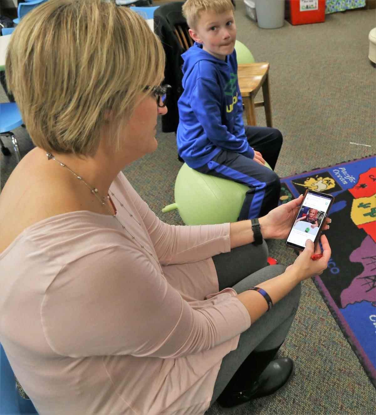 Abby Leonard shows how ClassDojo works on her phone. Her son, Ben Logan, likes the app.