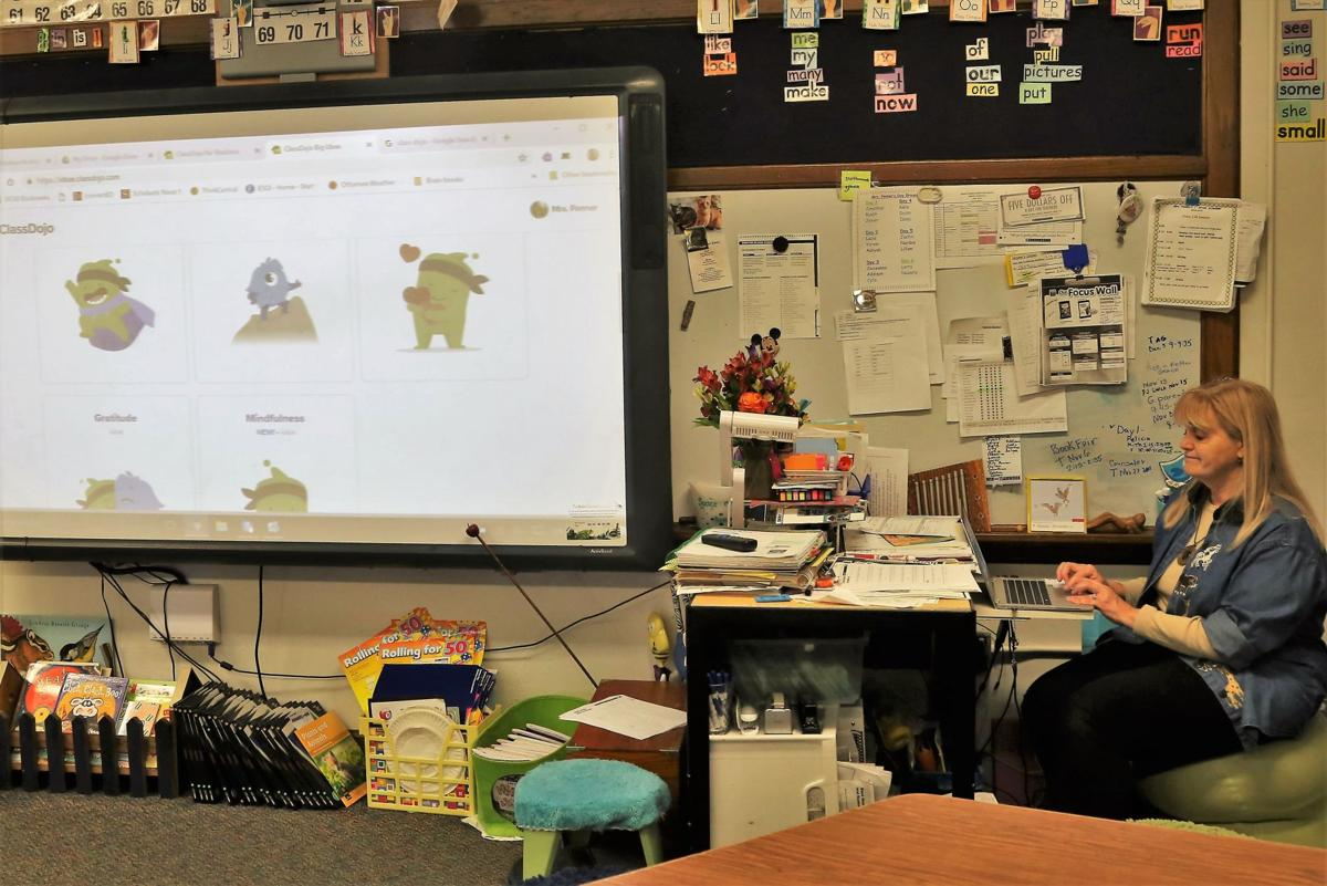 Emily Penner projects ClassDojo monster avatars on a screen in her classroom.