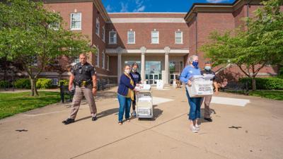 McCracken County Clerk's Office workers carry absentee ballots