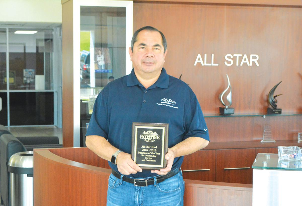 Fernando varela holding the award for business of the year varela is the owner of all star ford in palestine