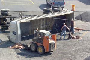 Two injured after asphalt truck overturns