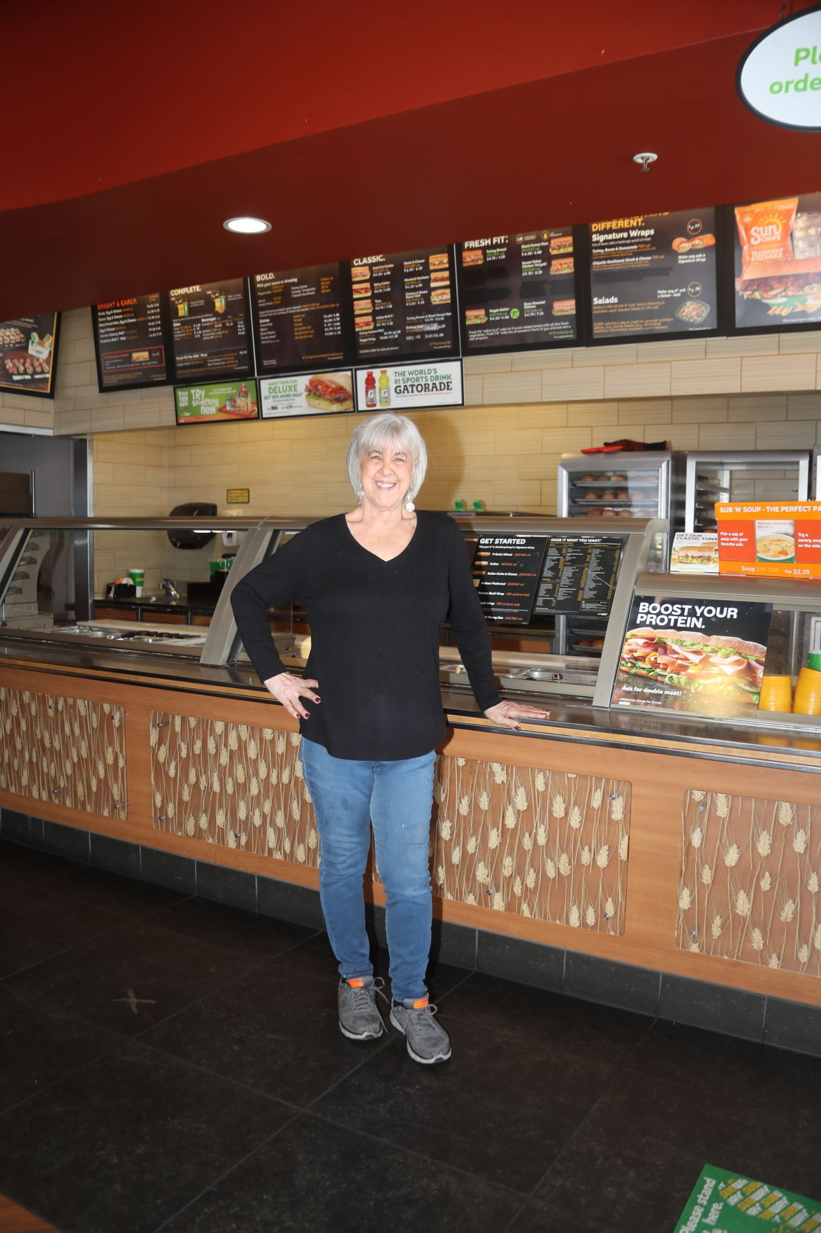 Kathy James Standing Alone In Front of Counter Vertical