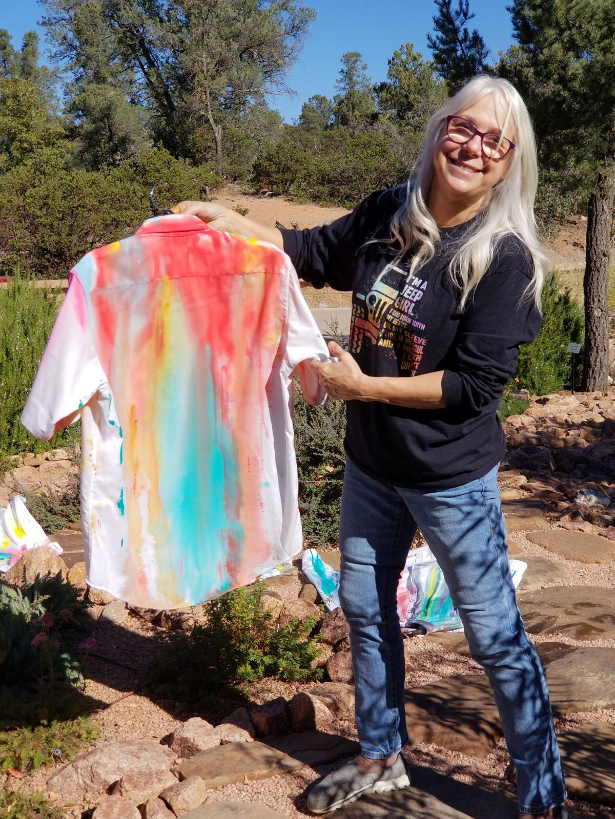 Mimi Rogers displays her painted shirt, created for the Student Art Show