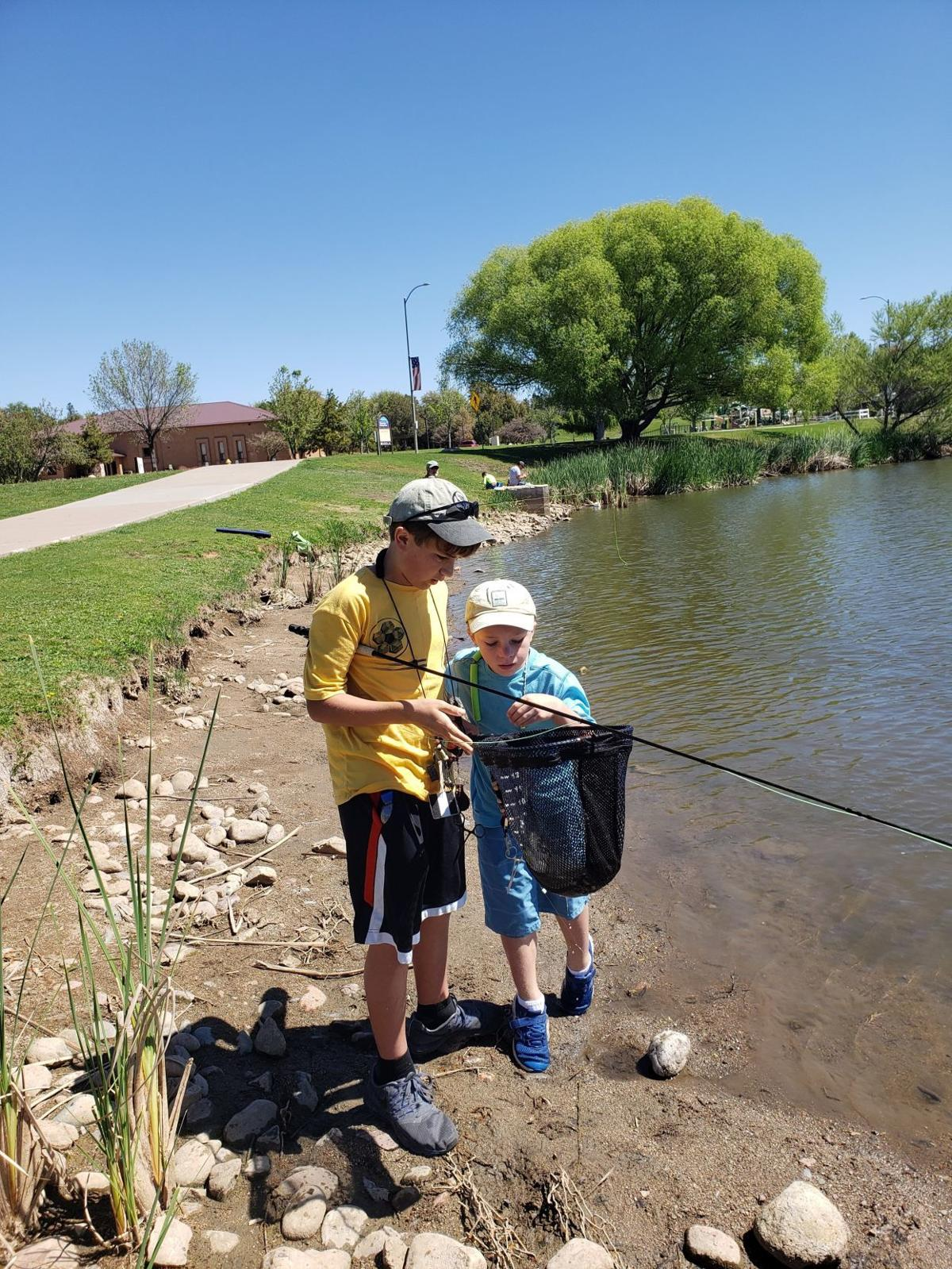 Owen and Ayden are admiring Owen's large trout, unhooking the fly and getting the fish ready for release. .jpg