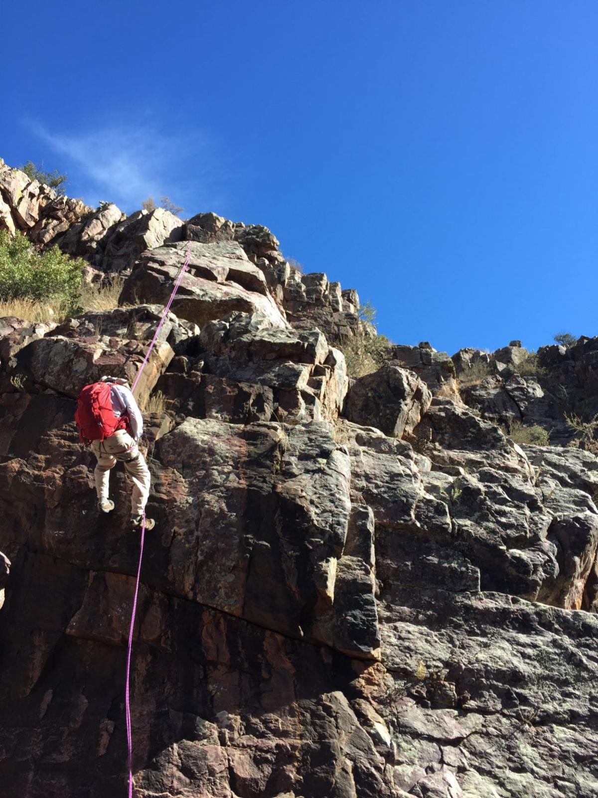 Joe Schmidt repels down a rock by Andrew Fiala
