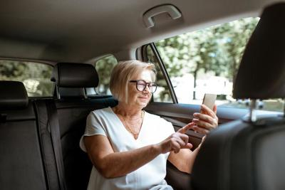 Senior woman with phone in the car