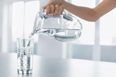 Drink Water. Woman's Hand Pouring Water From Pitcher Into A Glass. Healthy Lifestyle.