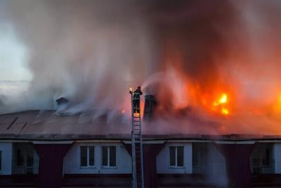 Burning fire flame with smoke on the apartment house roof in the city, firefighter or fireman on the ladder extinguishes fire