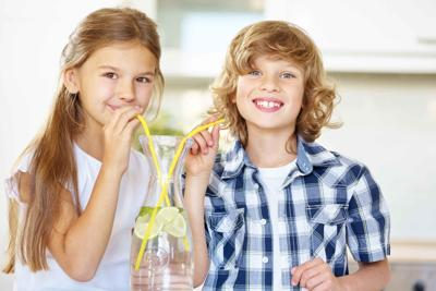 Boy and girl drinking water with straw