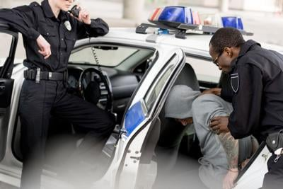 cropped shot of policewoman talking on radio set while her partner placing arrested man in car