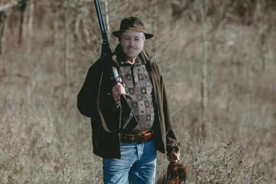 Contented solid hunter with gun and game