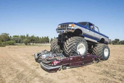 Monster truck over cars. Blue sky