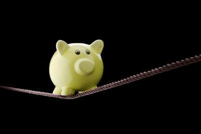 20926070 - piggy bank balancing on tightrope