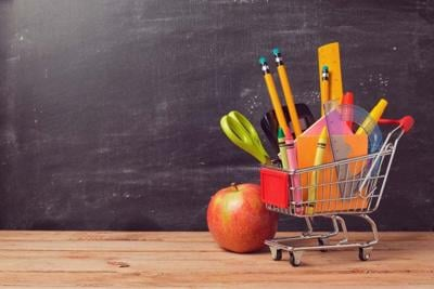 43530017 - shopping cart with school supplies over chalkboard background