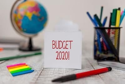 Text sign showing Budget 2020. Conceptual photo estimate of income and expenditure for next or current year Stationary and paper sheets plus small arrows with globe on the wooden desk.
