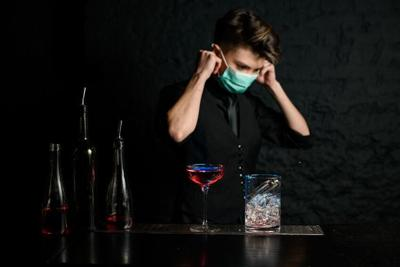 Young bartender puts on medical mask on bar counter.