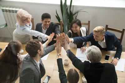 Diverse business team giving high five showing unity, top view