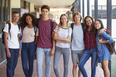 Teenage classmates standing in high school hallway