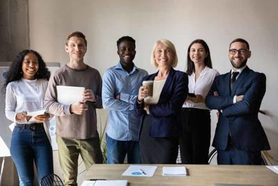 Happy confident diverse businesspeople stand together in office, team portrait