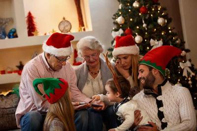 Children with grandparents looking photos on cell phone