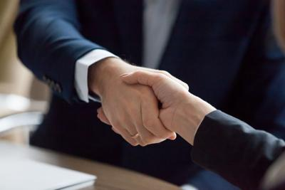 Businessman and businesswoman in suits handshaking showing partner respect, closeup