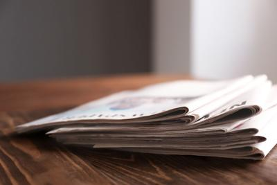 Pile of newspapers on wooden table