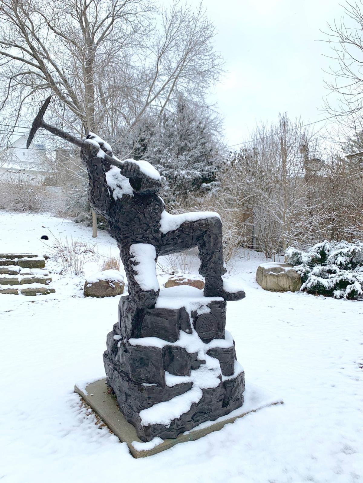 Snow-covered coal miner statue
