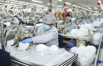 In this photo released by Xinhua News Agency, workers produce face masks in the workshop of a textile company in Jimo District of Qingdao in eastern China's Shandong Province on Wednesday. Qingdao Municipal Bureau of Industry and Information Technology has mobilized two large textile companies to produce face masks to help the fight against the novel coronavirus epidemic. — Liang Xiaopeng/Xinhua via AP
