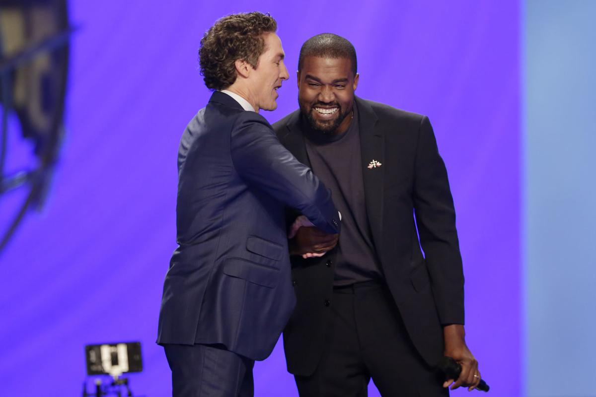 Rapper Kanye West, right, shakes hands with Joel Osteen. — AP Photo/Michael Wyke
