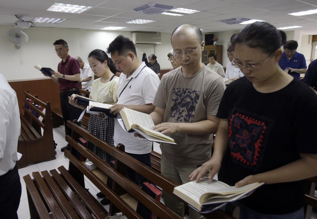 From right; Ren Dejun, Liao Qiang, Peng Ran and Ren Ruiting follow a hymn book during service at a church in Taipei, Taiwan. The Sunday service this week at an unassuming church in Taiwan was especially moving for one man, Liao Qiang. It was the first time he had worshipped publicly since authorities shut down his church in China seven months ago. — AP Photo/Chiang Ying-ying