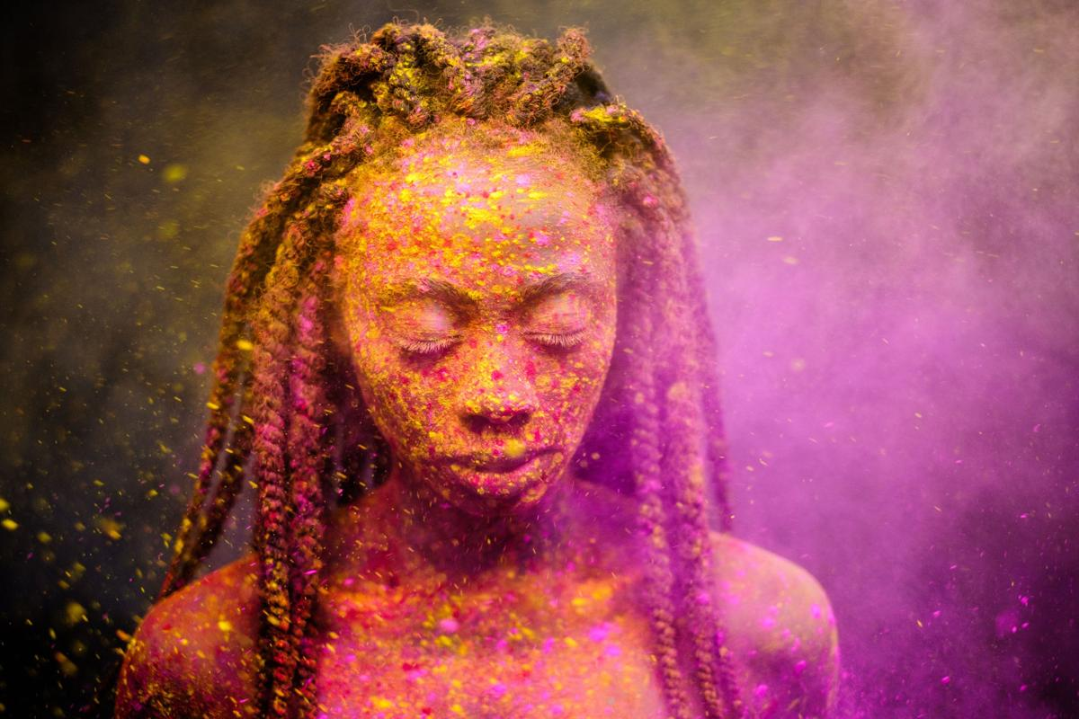 African woman with colourful powder on her face and body